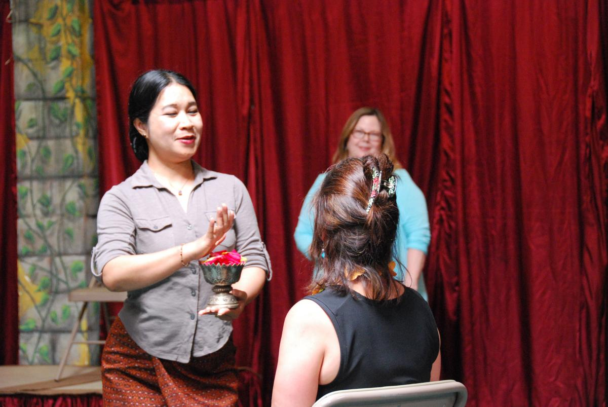 Bay Area Cambodian Classical Dancer Charya Burt gives Lily a traditional blessing as Director Amy Kitchener looks on.